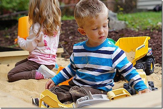 Hard at work in the sandbox, making roads & tractor tracks
