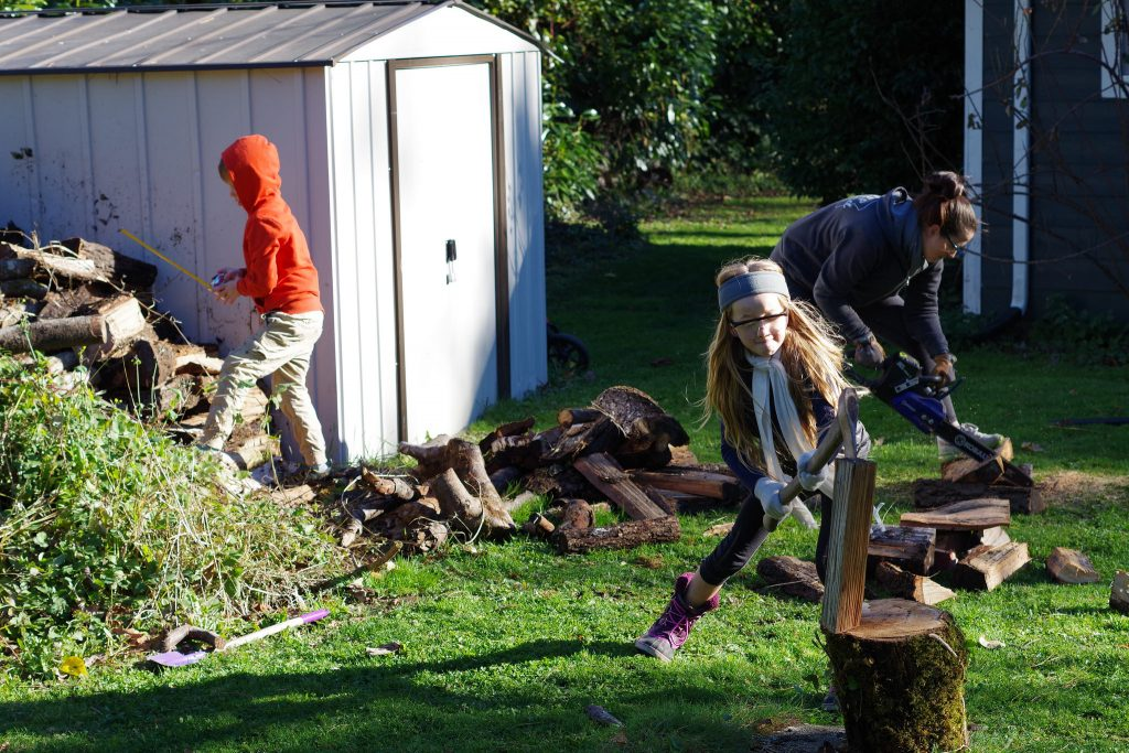 My 6-year-old son measuring firewood while my 8-year-old daughter splits kindling, and mommy handles the chainsaw.