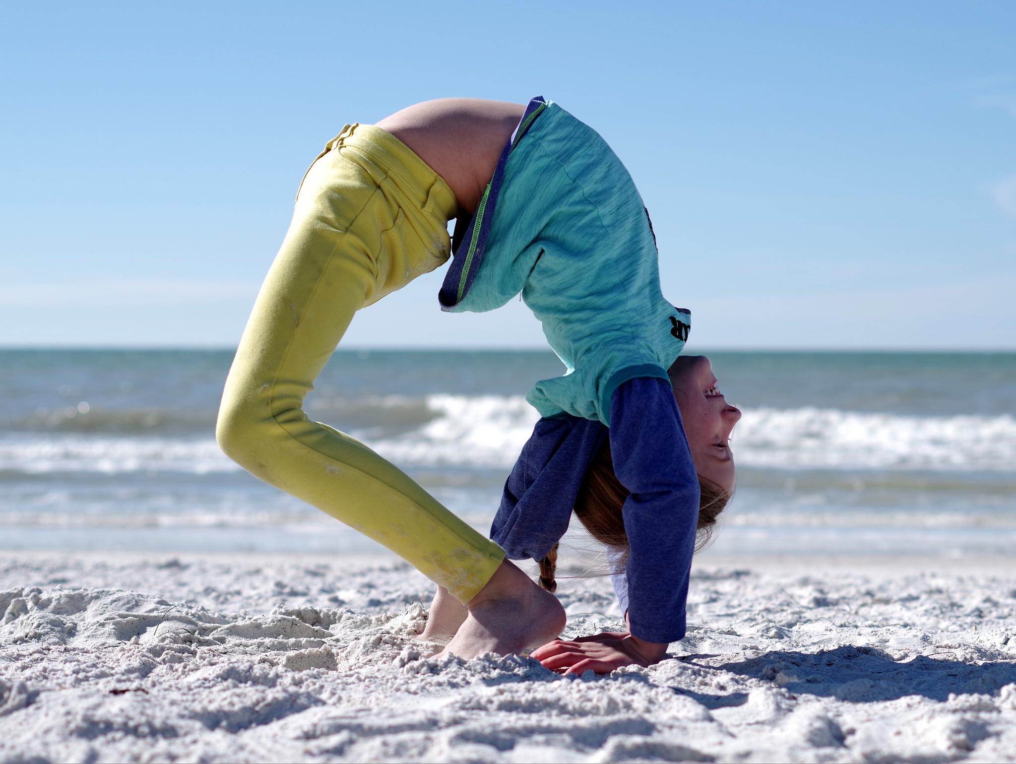 Practicing gymnastics at the beach